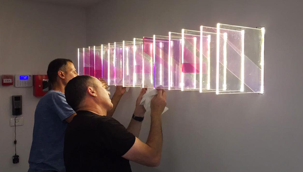 אלמנט תאורה בכניסה למשרדים – משחק שכבות היוצר אשליה אופטית המשתמש בלוגו החברה.